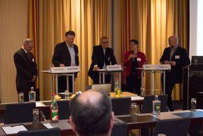 Podiumsdiskussion, Teilnehmer/-innen stehend vorm Auditorium