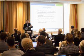 Vortragender vorn mit PowerPoint-Präsentation, sprechend zu den Teilnehmer/-innen